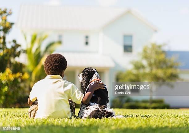 USA, Florida, Jupiter, Back view of boy (6-7 ) sitting with dog