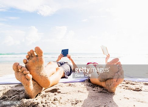 USA, Florida, Jupiter, Close-up of sand-covered feet of young couple lying on blanket on beach reading