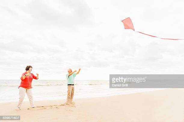 USA, Florida, Jupiter, Couple flying kite together on beach