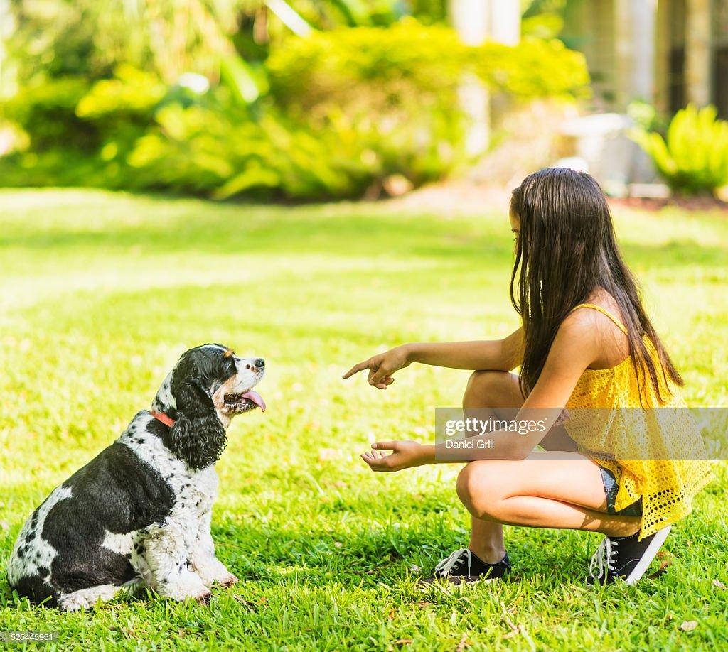 USA, Florida, Jupiter, Girl ( 8-9 ) teaching dog tricks