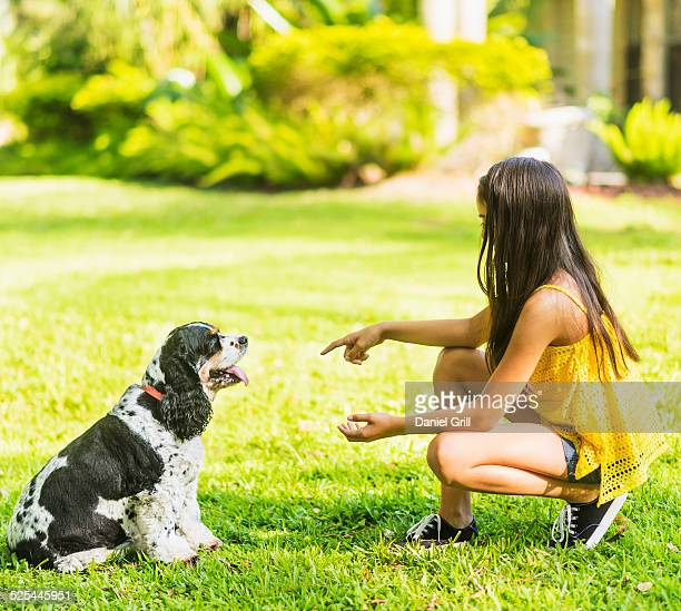 USA, Florida, Jupiter, Girl ( 8-9 ) teaching dog tricks