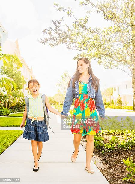 USA, Florida, Jupiter, Girl (6-7) walking to school with her mom