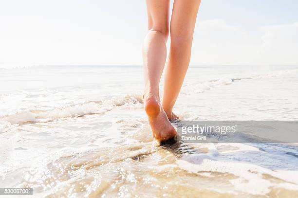 USA, Florida, Jupiter, Legs of woman walking in sea