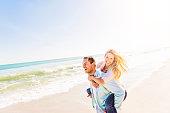 USA, Florida, Jupiter, Man giving woman piggyback ride