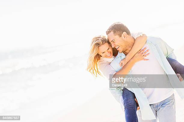 USA, Florida, Jupiter, Man giving woman piggyback ride