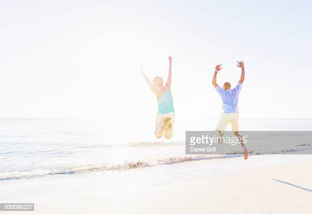 USA, Florida, Jupiter, Mature couple jumping in sea with arms raised