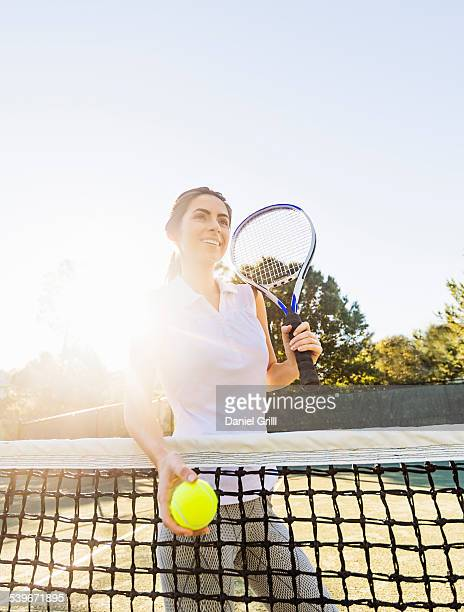 USA, Florida, Jupiter, Portrait of young woman standing by net, holding tennis ball and tennis racket