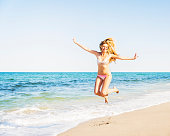 USA, Florida, Jupiter, Portrait of young woman wearing bikini jumping on beach