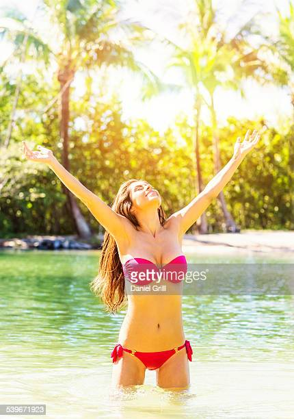 USA, Florida, Jupiter, Portrait of young woman wearing bikini standing in waters of tropical lagoon, raising arms