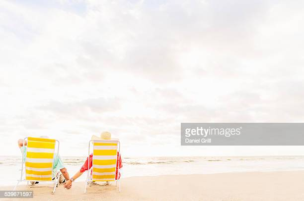 USA, Florida, Jupiter, Rear view of couple sitting in lounge chairs on beach