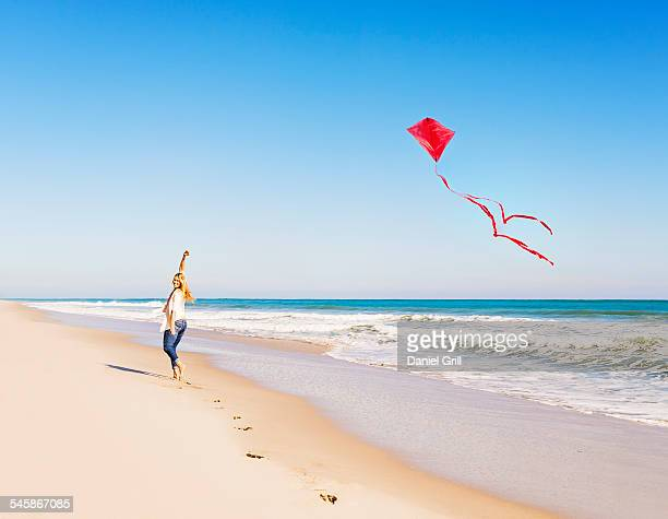 USA, Florida, Jupiter, Woman on beach with kite