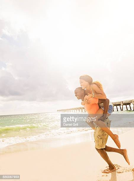 USA, Florida, Jupiter, Young couple playing on beach