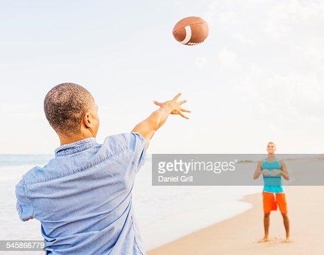 USA, Florida, Jupiter, Young men playing football on beach
