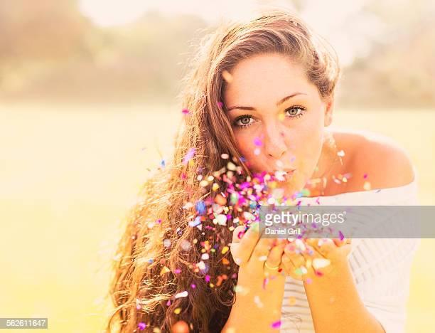 USA, Florida, Jupiter, Young woman blowing confetti