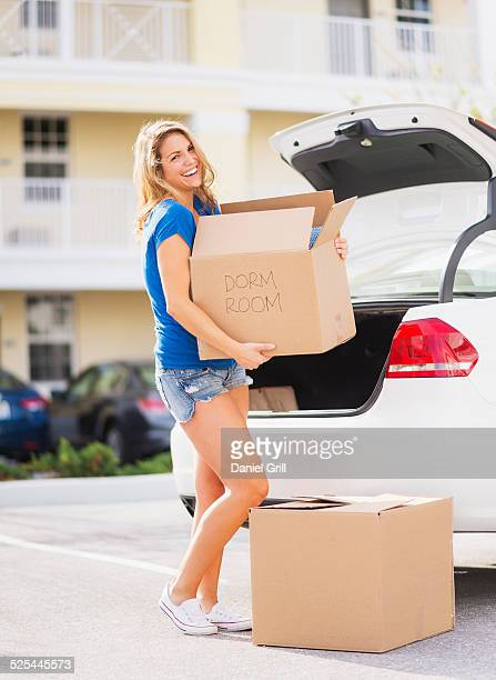USA, Florida, Jupiter, Young woman carrying box from car into her new house