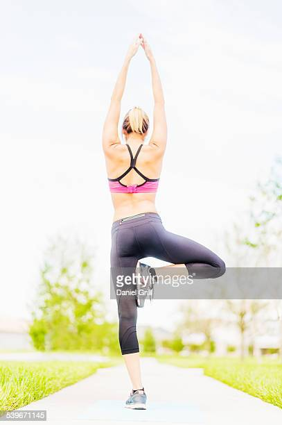 USA, Florida, Jupiter, Young woman doing yoga in park