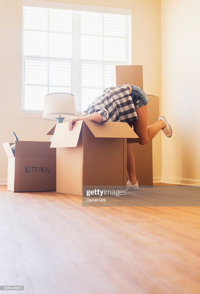 USA, Florida, Jupiter, Young woman looking into box in her new house