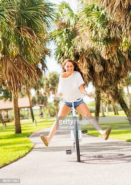 USA, Florida, Jupiter, Young woman riding bicycle in park