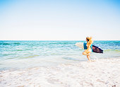 USA, Florida, Jupiter, Young woman running in surf into sea carrying surfboard
