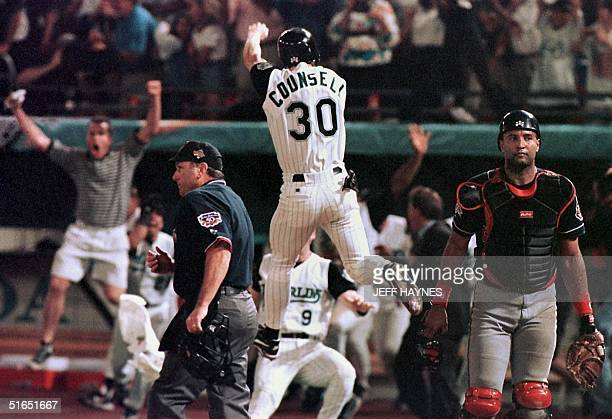 Florida Marlins player Craig Counsell jumps in the air after crossing the plate with the winning run as Cleveland Indians catcher Sandy Alomar walks...
