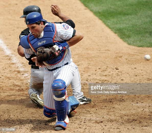 Florida Marlins' shortstop Alex Gonzalez scores on a sacrifice fly as the ball hurtles past New York Mets' catcher Mike Piazza in the seventh inning...