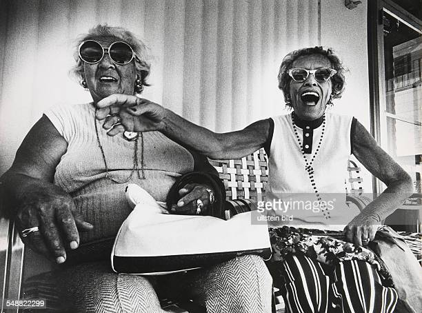 Anna Kronenfeld and Sadye Weiss share a joke on the porch in front of the George Washington Hotel on Collins Avenue