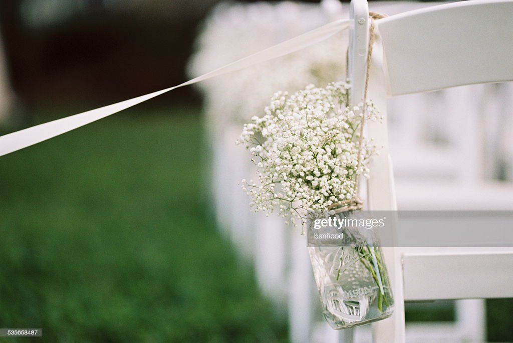 USA, Florida, Orange County, Winter Park, Close-up shot of bunch of babys breath flowers in a mason jar and white ribbon attached to back of white chair