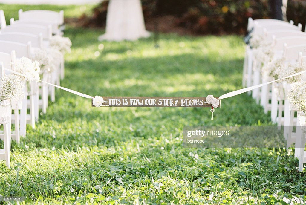 USA, Florida, Orange County, Winter Park, Wedding banner attached to white ribbon hanging across aisle between rows of white chairs on grass