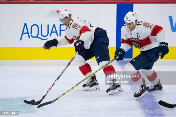 Florida Panthers Center Derek MacKenzie and Center Vincent Trocheck both reach for the puck in the third period during the game between the Florida...
