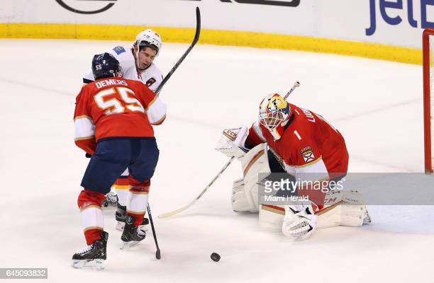 Florida Panthers goalie Roberto Luongo makes a save against the Calgary Flames' Sean Monahan as Monahan collides with Florida defenseman Jason Demer...