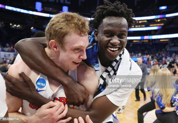 Florida players Canyon Barry left and Gorjok Gak celebrate after a 6539 win against Virginia during the second round of the NCAA Tournament at the...