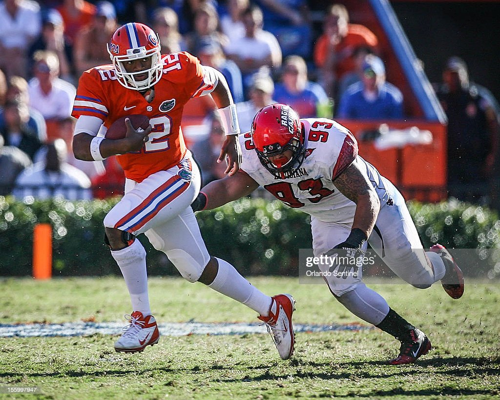 Florida quarterback Jacoby Brissett (12) evades Louisiana-Lafayette's Cordian Hagans (93) as he runs for yardage in the fourth quarter at Ben Hill Griffin Stadium on Saturday, November 10, 2012, in Gainesville, Florida. The host Gators rallied for a 27-20 win.