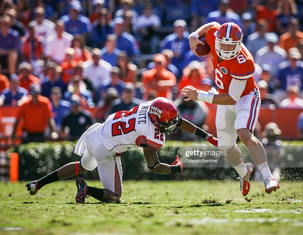 Florida quarterback Jeff Driskel (6) runs for yardage while evading Louisiana-Lafayette's Melvin White (22) in the first quarter at Ben Hill Griffin Stadium on Saturday, November 10, 2012, in Gainesville, Florida. The host Gators rallied for a 27-20 win.