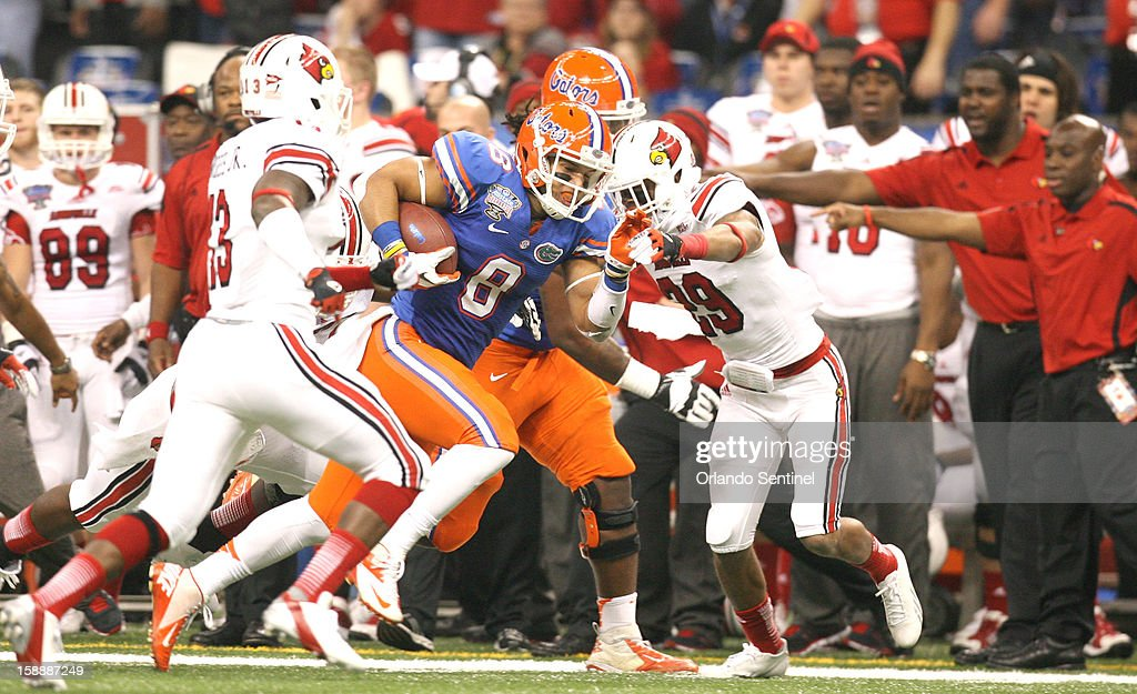 Florida running back Trey Burton, middle, fights for yardage against the Louisville defense in the Allstate Sugar Bowl at the Mercedes-Benz Superdome on Wednesday, January 2, 2013, in New Orleans, Louisiana.