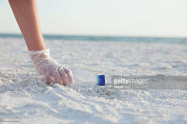 USA, Florida, St. Petersburg, Girl (10-11) collecting plastic bottle on beach