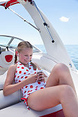USA, Florida, St. Petersburg, Girl (10-11) listening to mp3 player on boat at sea