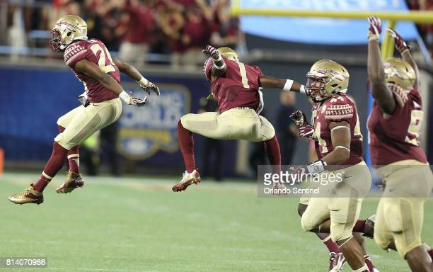 Florida State defensive back Marcus Lewis and teammates celebrate after Lewis intercepted a pass during the Florida State vs University of...