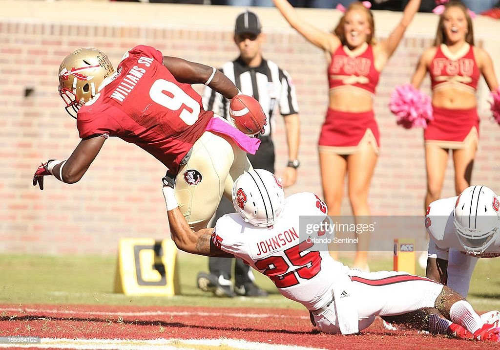 Florida State running back Karlos Williams (9) leaps into the end zone to finish an 18-yard touchdown run as North Carolina State cornerback Dontae Johnson (25) tries to stop him at Doak Campbell Stadium in Tallahassee, Florida, on Saturday, October 26, 2013.