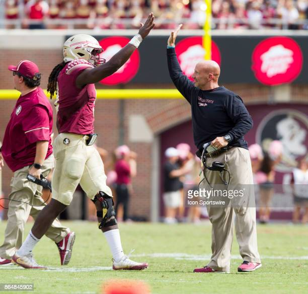 Florida State Seminoles defensive end Josh Sweat high fives with defensive coordinator Charles Kelly during the game between the Louisville Cardinals...