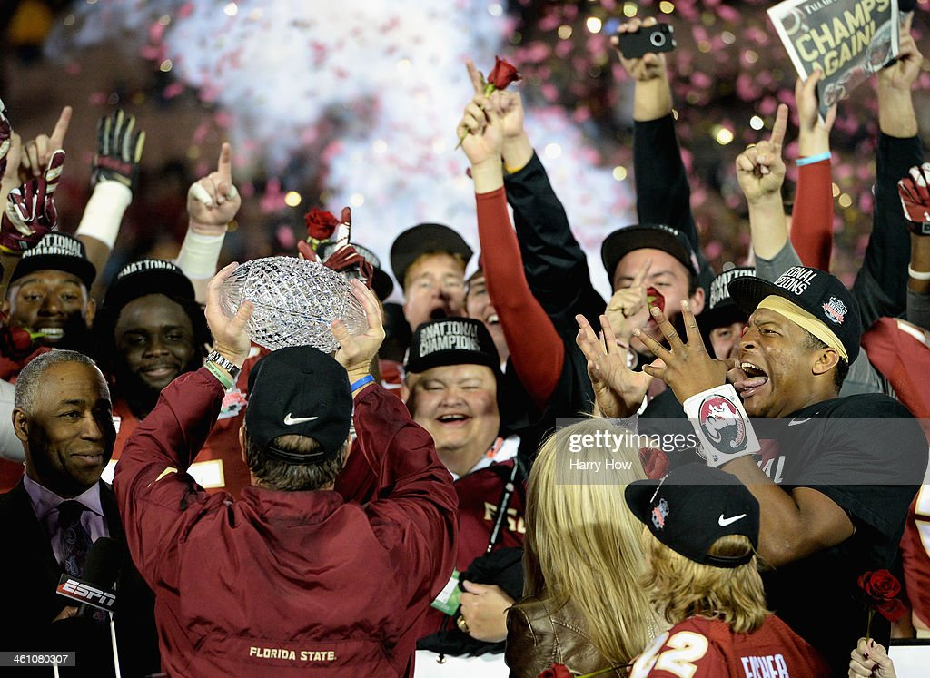 Florida State Seminoles head coach <a gi-track='captionPersonalityLinkClicked' href=/galleries/search?phrase=Jimbo+Fisher&family=editorial&specificpeople=4505734 ng-click='$event.stopPropagation()'>Jimbo Fisher</a> holds the Coaches' Trophy as quarterback <a gi-track='captionPersonalityLinkClicked' href=/galleries/search?phrase=Jameis+Winston&family=editorial&specificpeople=8772860 ng-click='$event.stopPropagation()'>Jameis Winston</a> (R) #5 looks on after defeating the Auburn Tigers 34-31 in the 2014 Vizio BCS National Championship Game at the Rose Bowl on January 6, 2014 in Pasadena, California.