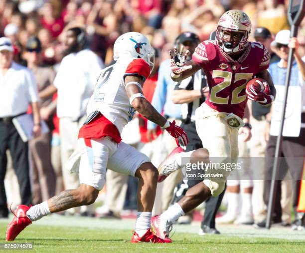 Florida State Seminoles running back Amir Rasul stiff arms Delaware State Hornets defensive back Cartier Wilkins during the game between the Delaware...