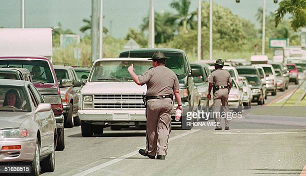 Florida State Troopers direct traffic outside FLorida City Florida 26 September as residents of the Florida Keys wait on US1 for hours to return to...