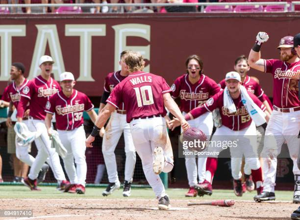 Florida State's Taylor Walls runs in to score the game wining run and celebrates with his teammates after a Jackson Lueck base hit during the NCCA...