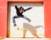 USA, Florida, West Palm Beach, Man jumping on skateboard against closed garage door