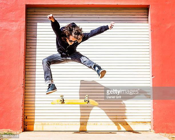 USA, Florida, West Palm Beach, Man jumping on skateboard against closed garage door