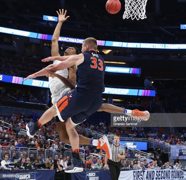 Florida's Devin Robinson left is fouled hard by Virginia's Jack Salt during the second round of the NCAA Tournament at the Amway Center in Orlando...