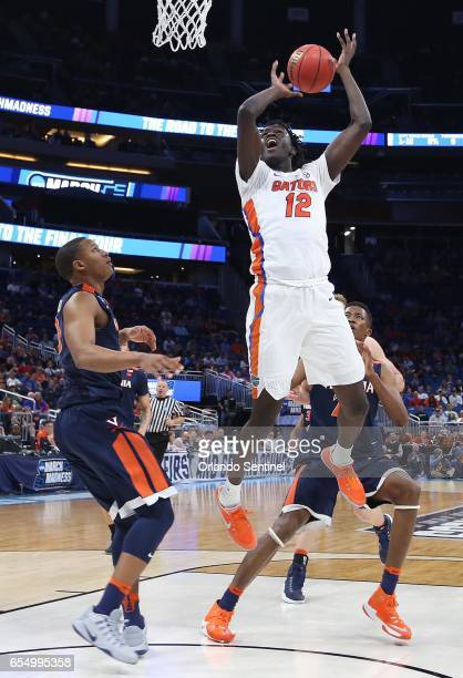 Florida's Gorjok Gak leaps for a rebound against Virginia during the second round of the NCAA Tournament at the Amway Center in Orlando Fla on...