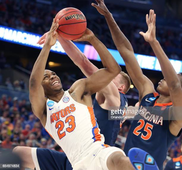 Florida's Justin Leon battles Virginia's Mamadi Diakite during the second round of the NCAA Tournament at the Amway Center in Orlando Fla on Saturday...