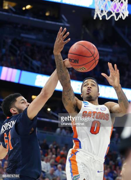Florida's Kasey Hill and Virginia's Darius Thompson battle for a rebound during the second round of the NCAA Tournament at the Amway Center in...