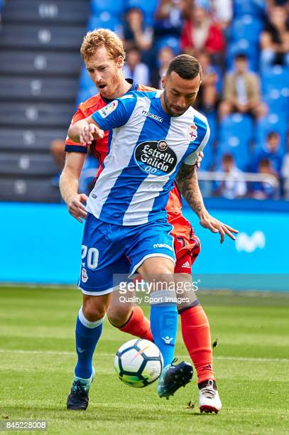 Florin Andone of Deportivo de La Coruna is challenged by David Zurutuza of Real Sociedad during the La Liga match between Deportivo La Coruna and...